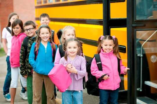 A group of children getting onto a school bus