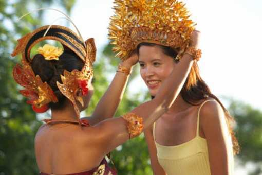 Indonesian dancer putting traditional headwear on female tourist's head