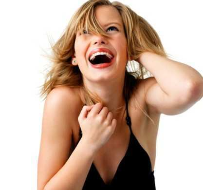 Attractive young woman with hand in hair, laughing