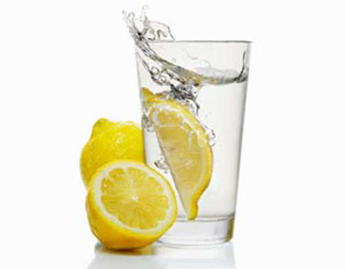 A wedge of lemon falling into a glass of water