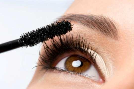 Woman applying mascara on her eyelashes - macro shot