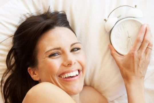 Woman-In-Bed-With-Alarm-Clock