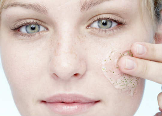 Young woman applying exfoliating gel to face, portrait, close-up