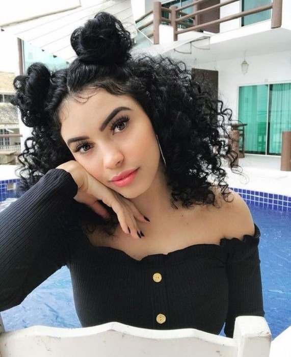 thick curly hairstyle with double buns